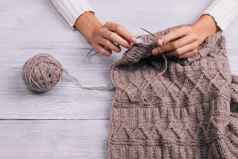 Zamyka up kobiety obsiadanie przy drewnianego stołu i puloweru dzianinami zdjęcie stock