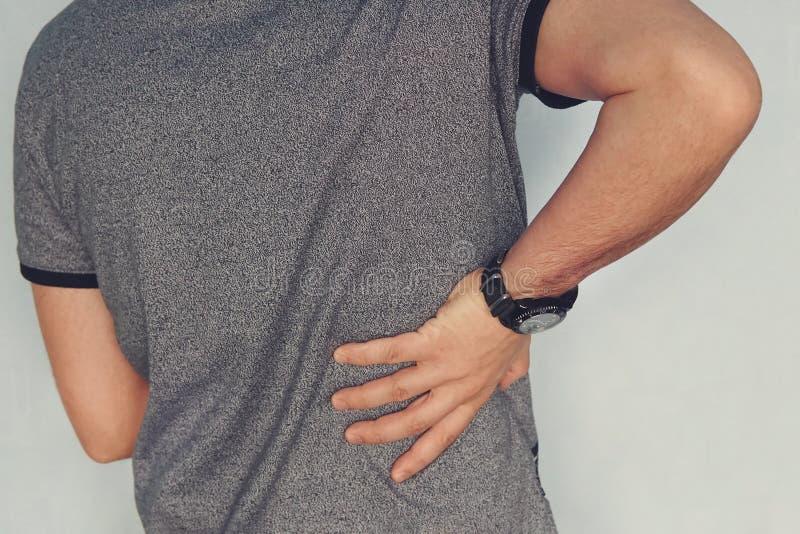 Zamyka up mężczyzna trzyma jego w bólu z powrotem Chory cynaderki ból w cynaderkach nerkowy niepowodzenie pacjent trzyma jego ręk obrazy stock