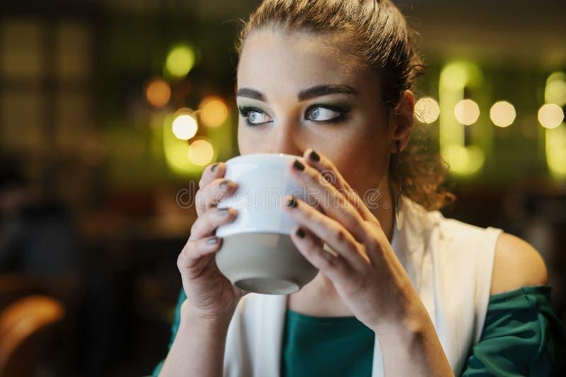 Zamyka up młoda brunetki kobieta pije kawę zdjęcia royalty free