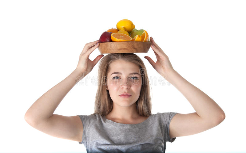 Zamyka up młoda kobieta która trzyma drewnianego puchar z owoc: jabłka, pomarańcze, cytryna Witaminy i zdrowy łasowanie zdjęcie stock