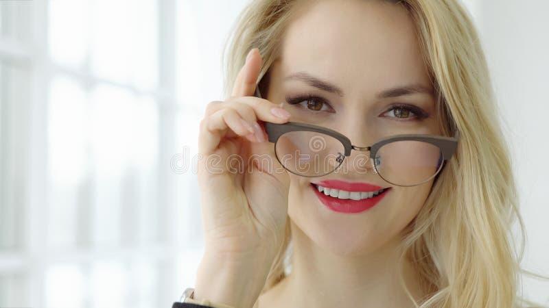 Zamyka up młoda piękna kobieta z szkłami i patrzeć kamerę przy okno fotografia stock