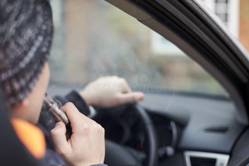 Zamyka Up młodego człowieka obsiadanie W Samochodowym Używa Vapourizer obrazy stock