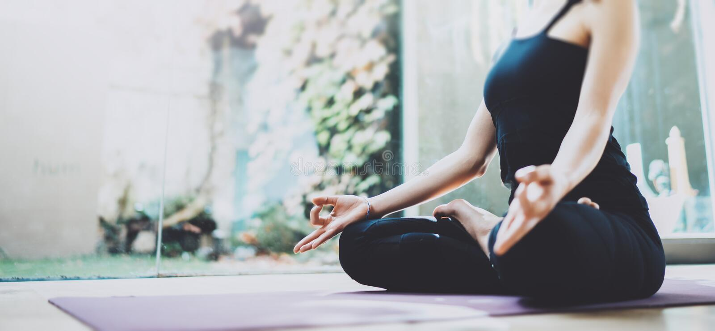 Zamyka up młodej kobiety ćwiczy joga w stażowej sala odizolowywająca pojęcie czarny wolność Calmness i relaksuje, żeński szczęści obraz royalty free