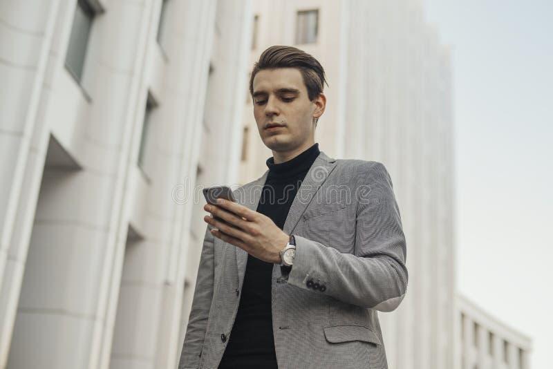 Zamyka up młody biznesmen opowiada telefonem komórkowym obok centrum biznesu fotografia stock