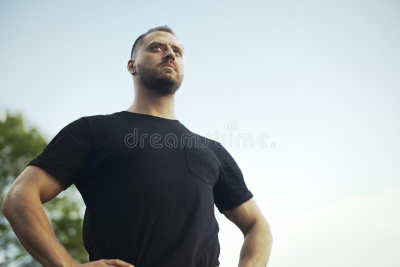 Zamyka up młody człowiek relaksuje przy parkiem po ćwiczyć w czarnym sportswear obrazy royalty free