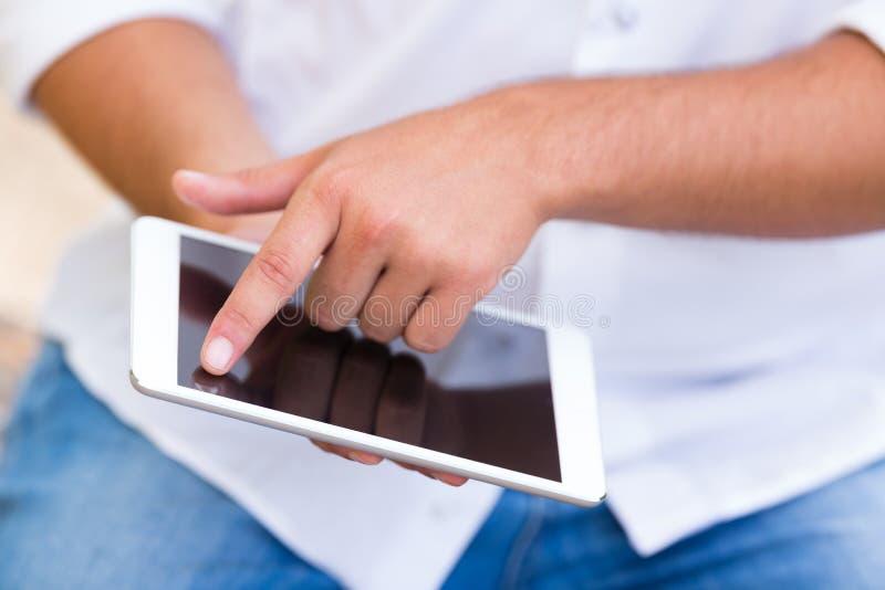 Zamyka up młody człowiek używa internet na cyfrowej pastylce zdjęcia stock