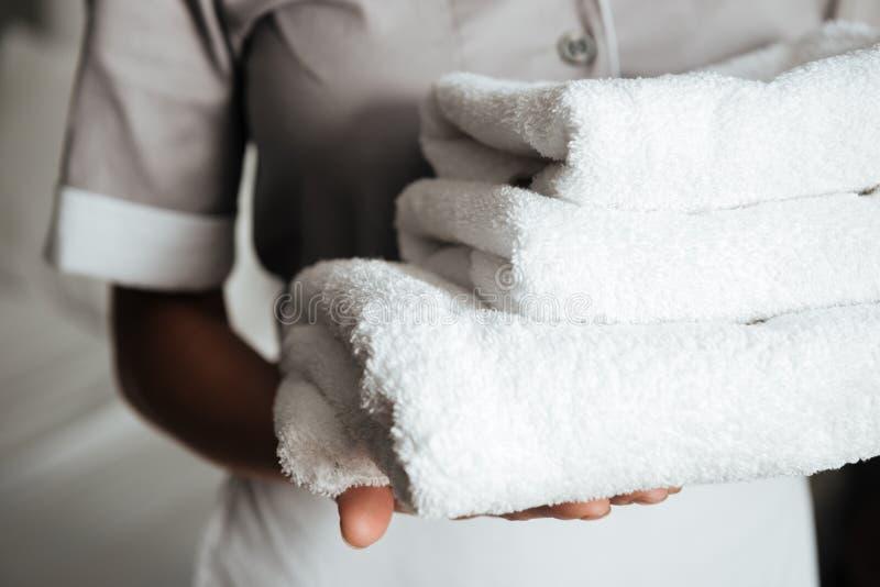 Zamyka up młody mienie składający gosposia ręczniki fotografia royalty free