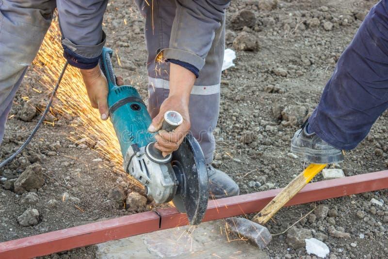 Zamyka up metalu pracownik używa kąta ostrzarza rżnięty metalu bar zdjęcie royalty free