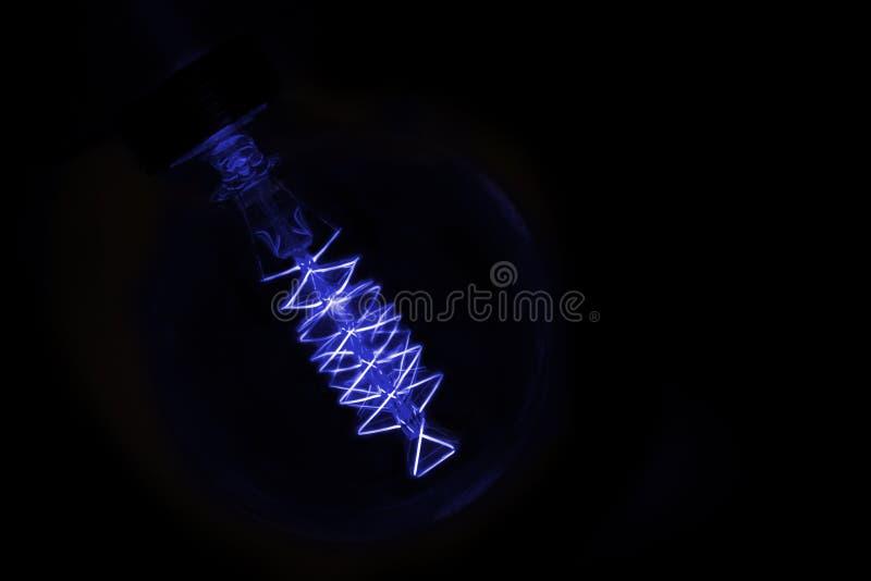 Zamyka up na błękitnej żarówce jarzy się w zmroku obraz stock