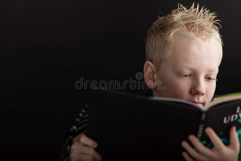 Zamyka up na chłopiec czytelniczej książce obraz royalty free