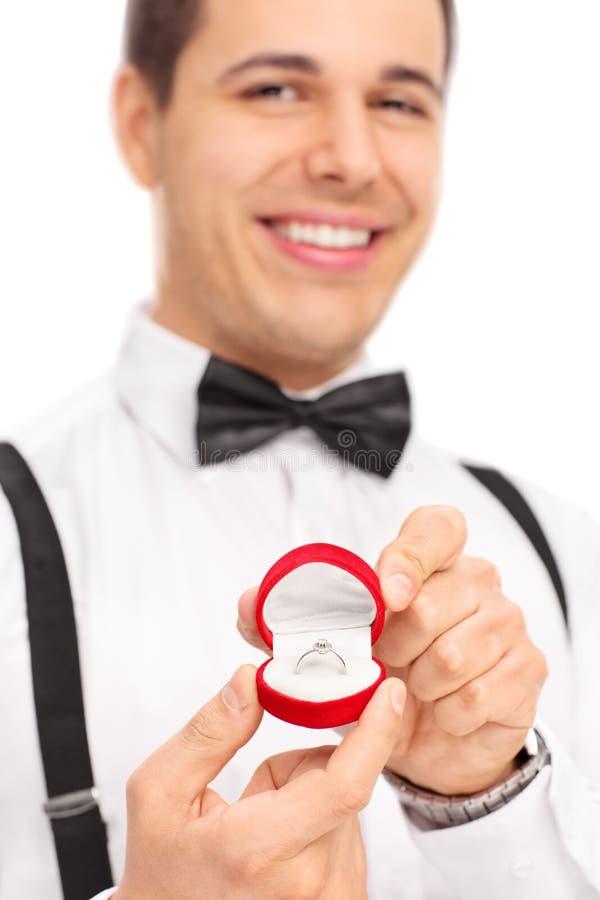 Zamyka up na młodym człowieku trzyma pierścionek zaręczynowego zdjęcia royalty free