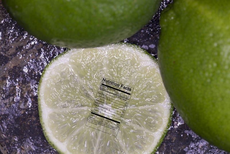 Zamyka up na plasterku wapno z świeżymi wapno z odżywianie etykietką fotografia stock