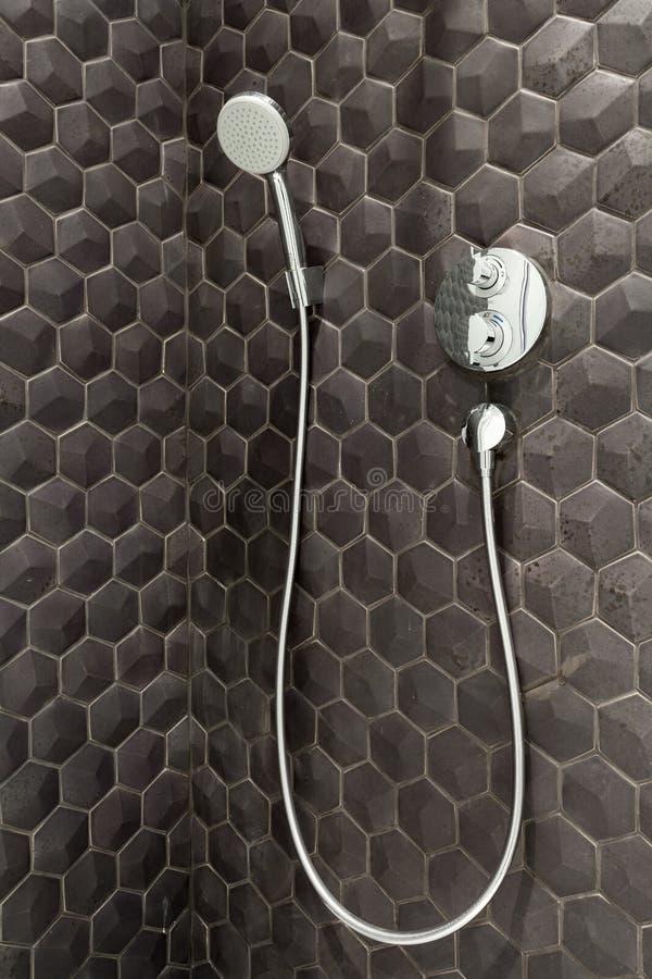 Zamyka up nowa podeszczowej prysznic głowa w łazience przeciw tłu czarne płytki obraz stock