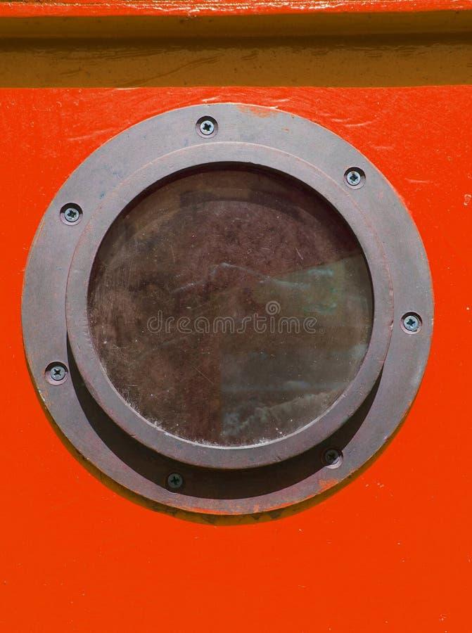 zamyka up ośniedziały metalu rocznika porthole na czerwonej drewnianej łodzi zdjęcia stock