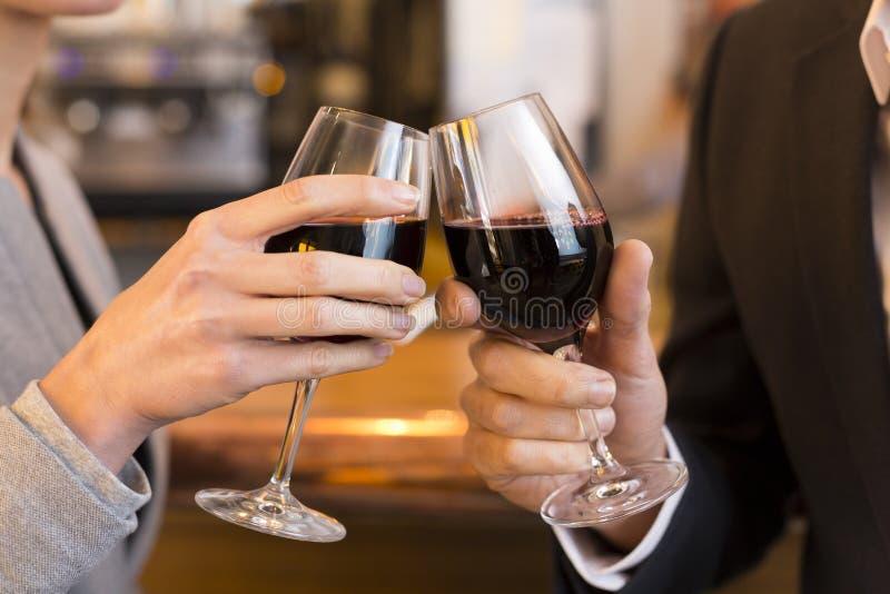 Zamyka Up para Wznosi toast z czerwonego wina szkłem w restauraci fotografia stock