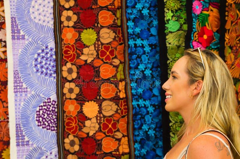 Zamyka up piękna blondynki młoda kobieta patrzeje andyjską tradycyjną odzież, kolorowy tkaniny tło obrazy royalty free