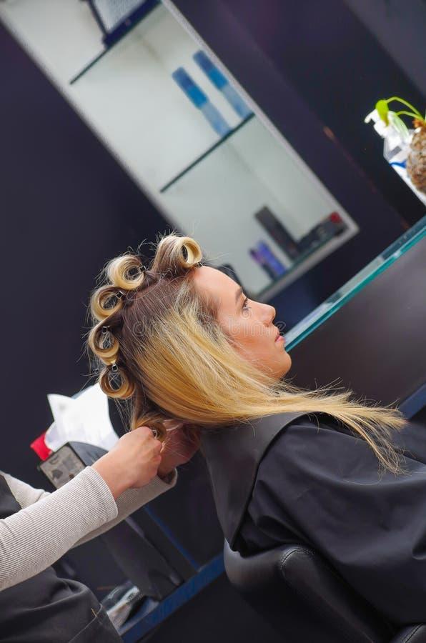 Zamyka up piękna kobieta w włosianym salonie z stylistą pracuje z curlers w głowie w włosianego salonu tle, obraz royalty free
