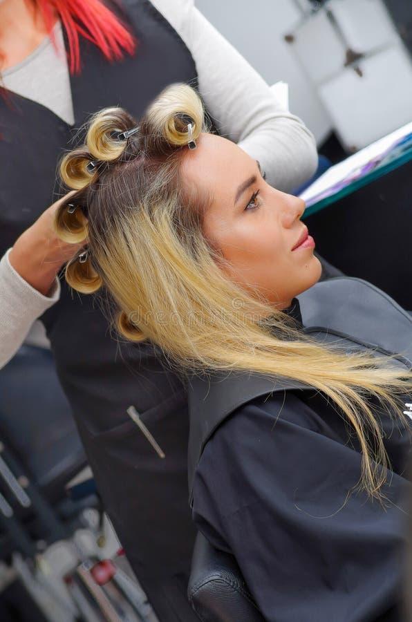 Zamyka up piękna kobieta w włosianym salonie z stylistą pracuje z curlers w głowie w włosianego salonu tle, obrazy royalty free