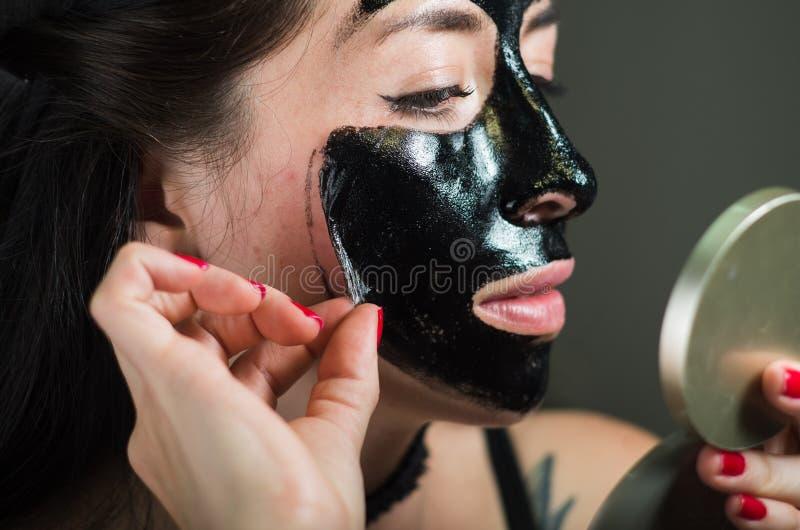 Zamyka up piękno młoda kobieta bierze daleko połówkę czarnej twarzy maska patrzeje lustro fotografia royalty free