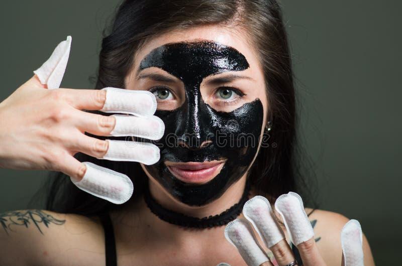 Zamyka up piękno młoda kobieta używa czarnej twarzy maskę i będący ubranym gwoździa ochraniacza w jej gwoździach, w czarnym tle obrazy stock