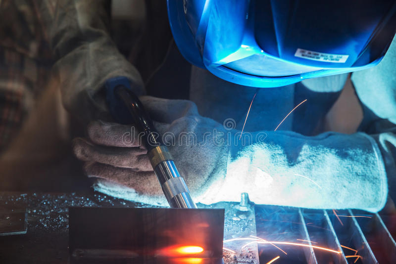 Zamyka up pracownik z ochronnej maski spawalniczym metalem selekcyjny obraz stock