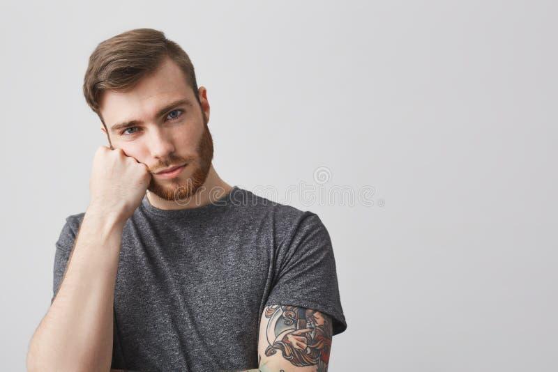 Zamyka up przystojny caucasian mężczyzna z brodą i tatuaż na ręki mienia głowie z ręką, patrzejący w kamerze z zanudzający zdjęcie stock