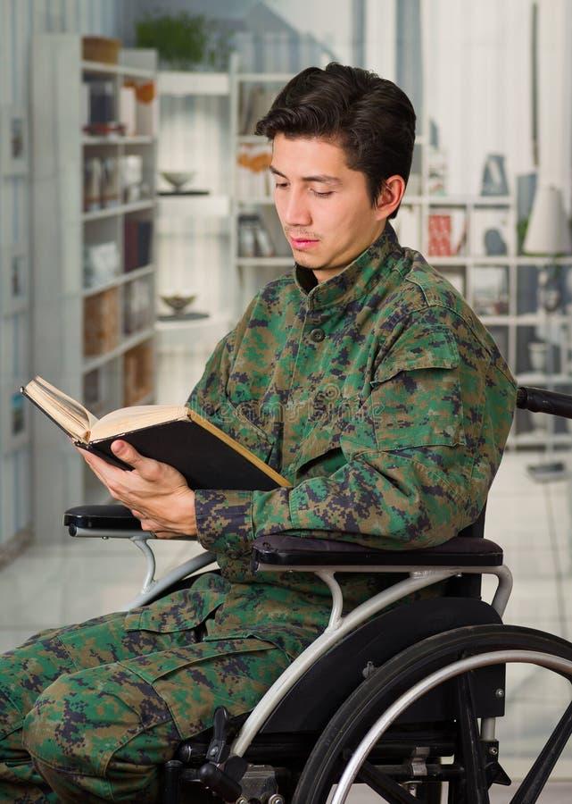 Zamyka up przystojny młody żołnierza obsiadanie na koła krześle czyta książkę w zamazanym tle w domu, obrazy stock