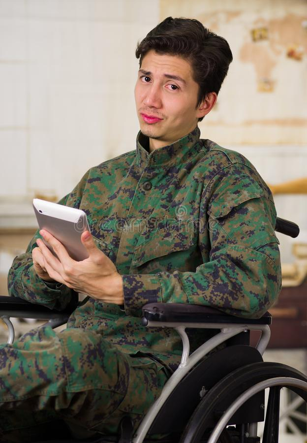 Zamyka up przystojny młody żołnierza obsiadanie na koła krześle używa jego pastylkę w zamazanym, będący ubranym wojskowego unifor zdjęcie stock