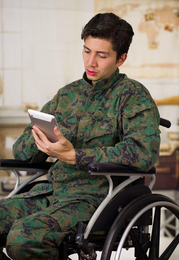 Zamyka up przystojny młody żołnierza obsiadanie na koła krześle używa jego pastylkę w zamazanym, będący ubranym wojskowego unifor fotografia stock