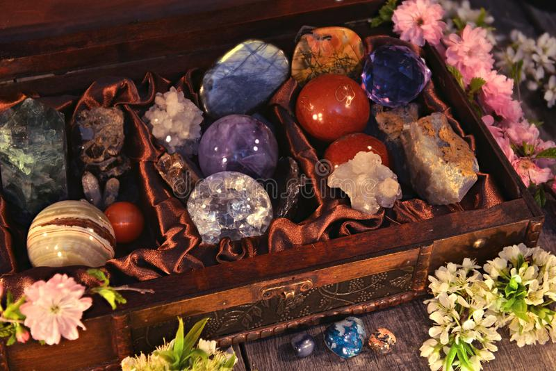 Zamyka up pudełko z magicznymi kryształami i kamieniami, Sakura wiosny kwiaty na deskach obraz stock