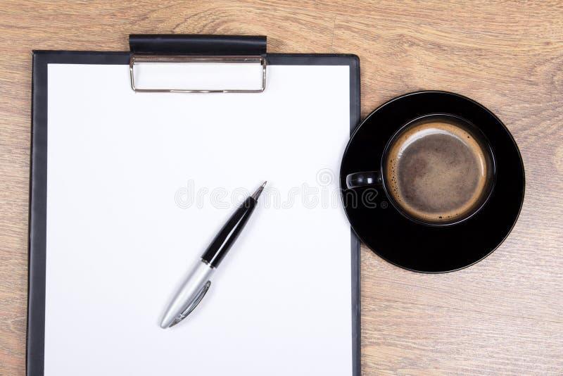 Zamyka up pusty schowek, pióro i filiżanka czarna kawa na drewnie, zdjęcie stock