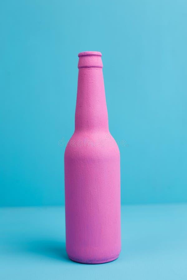 Zamyka up różowa piwna butelka na błękitnym tle Zwodniczo attra obrazy stock
