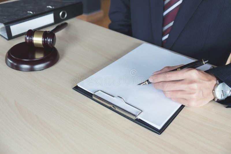 Zamyka up ręka, Męski prawnik pracuje z młoteczkiem i nutowy papier, obrazy stock