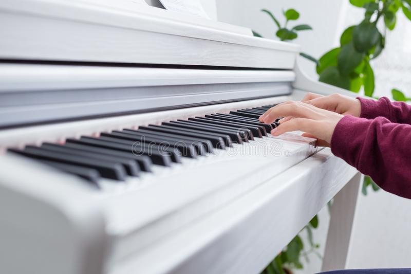 Zamyka up ręki bawić się pianino młoda dziewczyna zdjęcia royalty free