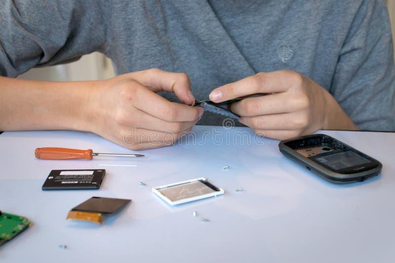 Zamyka up ręki naprawia telefon komórkowego obrazy stock