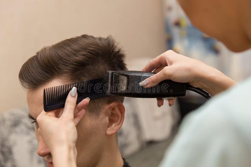 Zamyka up ręki robi ostrzyżeniu atrakcyjny mężczyzna w zakładzie fryzjerskim młody fryzjer męski fotografia royalty free