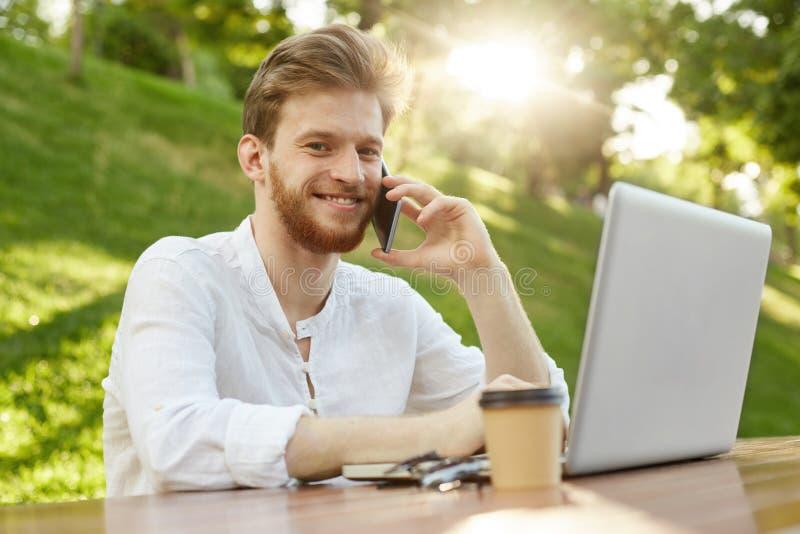 Zamyka up rozochocony miedzianowłosy facet z modnym włosy i brody siedzącym outside, pracujący na laptopie, opowiada dalej zdjęcia stock