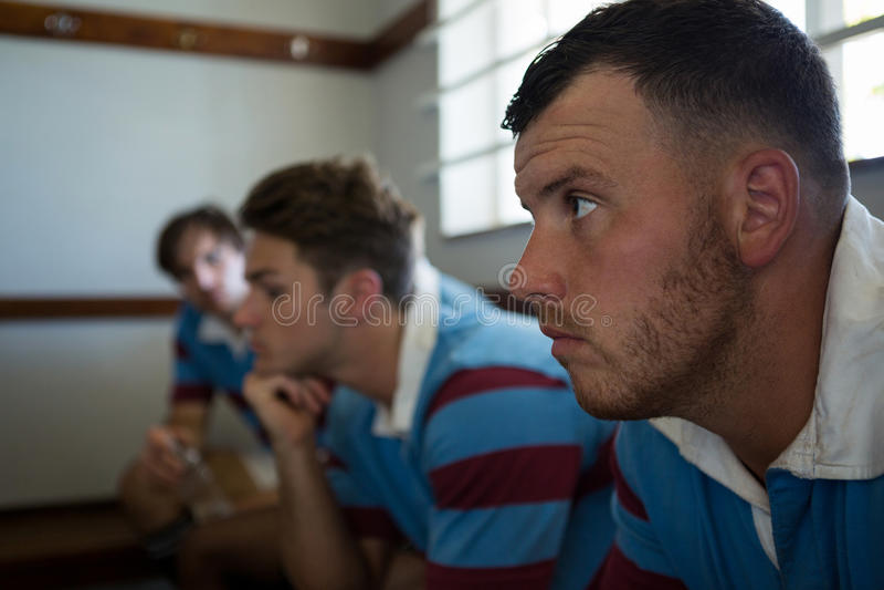 Zamyka up rozważni rugby gracze patrzeje oddalony podczas gdy siedzący przeciw ścianie fotografia stock