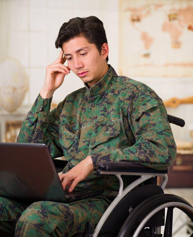 Zamyka up rozważny młody żołnierza obsiadanie na koła krześle używa jego komputer nad jego nogami, będący ubranym wojskowego unif zdjęcie royalty free