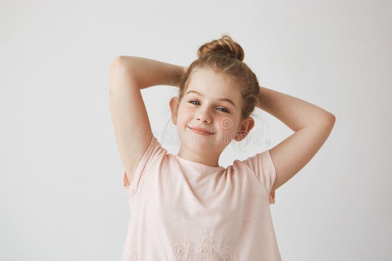 Zamyka up słodka mała blondynki dziewczyna ono uśmiecha się z babeczki uczesaniem w różowej koszulce, trzymający ręki za głową z  fotografia royalty free