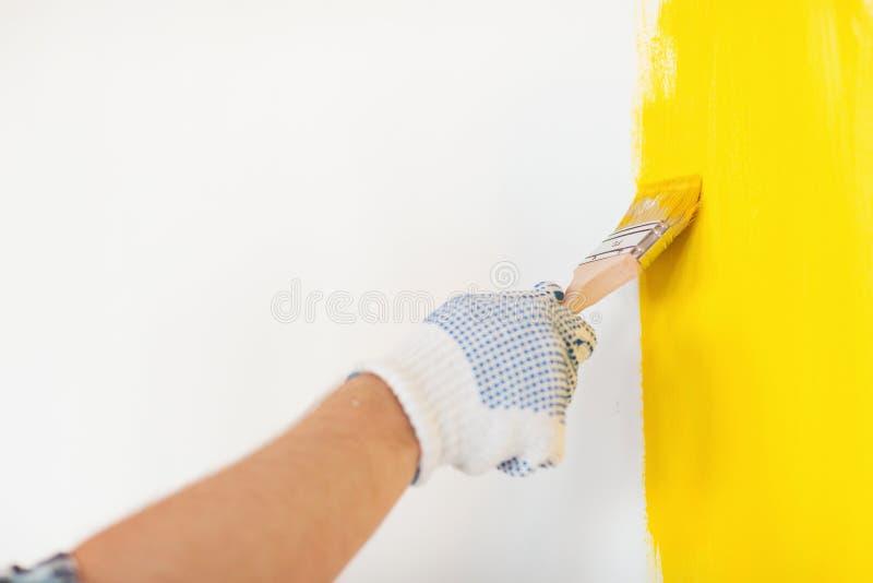 Zamyka up samiec trzyma paintbrush w rękawiczkach zdjęcie stock