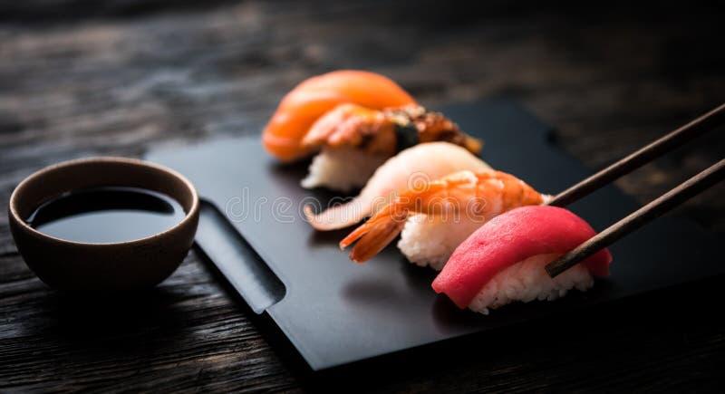 Zamyka up sashimi suszi ustawiający z chopsticks i sojami zdjęcie royalty free