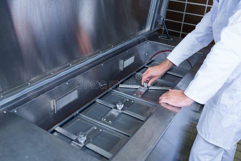 Zamyka up skupiający się piwowar pracuje przy maszyną obraz royalty free