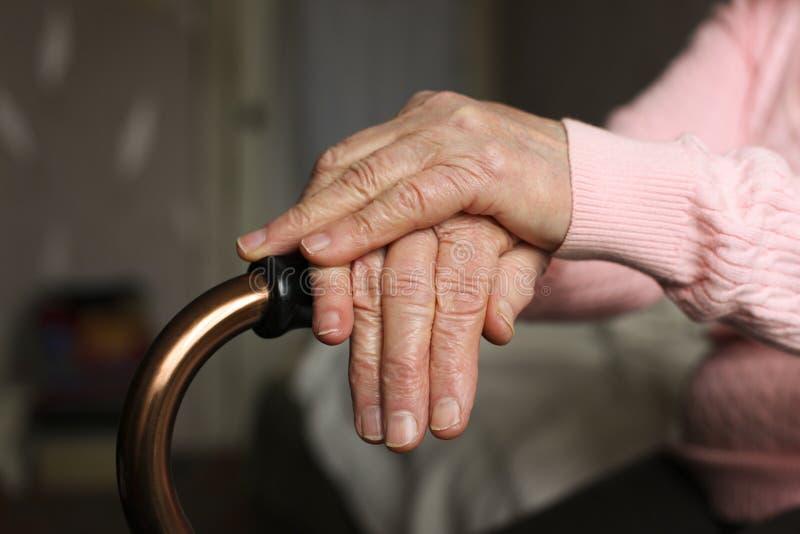 Zamyka up starsza kobieta trzyma chodzącej trzciny w karmiącym domu obrazy royalty free