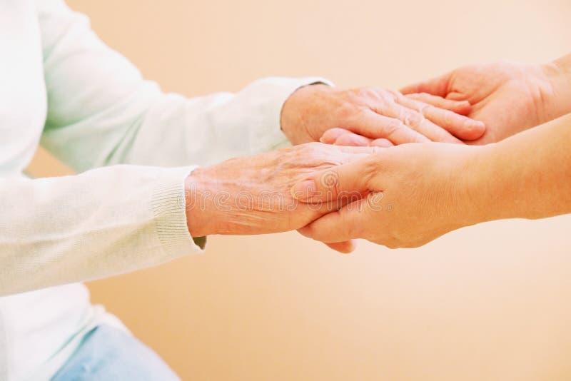 Zamyka up starsze kobiety i młodej kobiety mienia ręki Opieki i poparcia pojęcie zdjęcie stock
