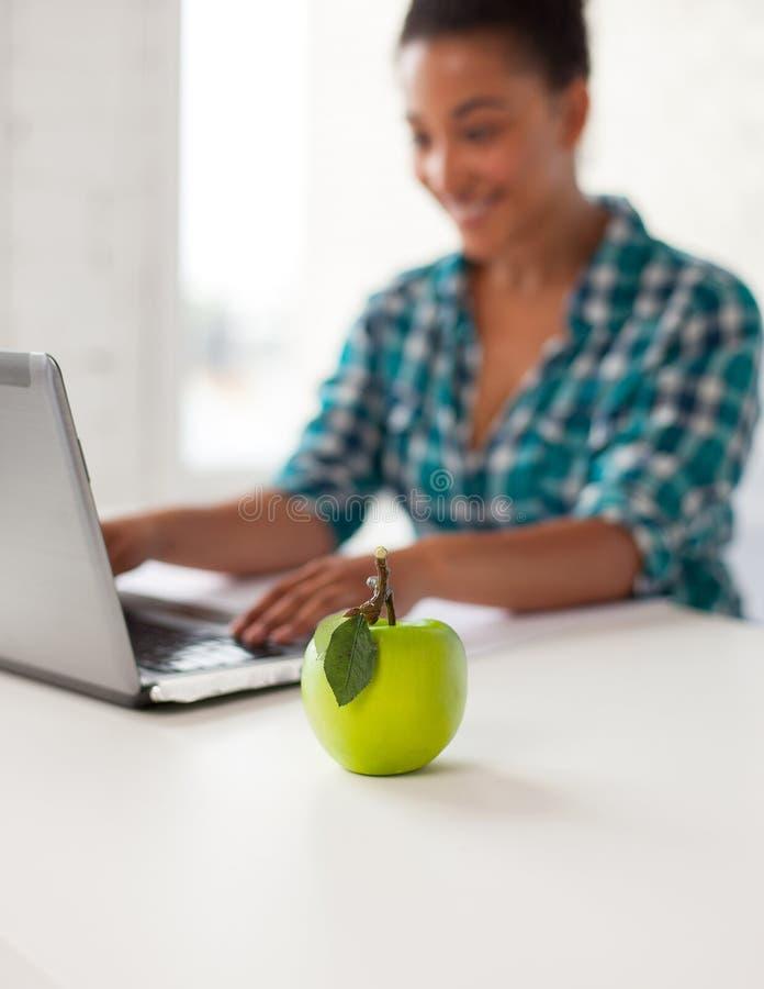Zamyka up studencka dziewczyna z laptopem i jabłkiem fotografia royalty free