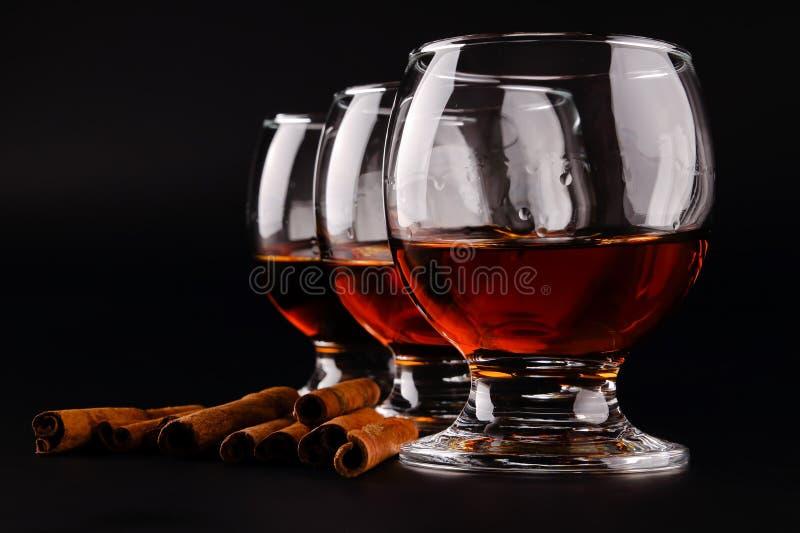 Zamyka up trzy czara szkła z koniakiem, ciemnym rum, brandy lub rozpraszający cynamonowi kije na czarnym tle z z rzędu, zdjęcia royalty free