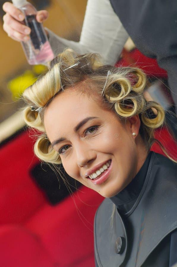 Zamyka up uśmiechnięta piękna kobieta w włosianym salonie z stylistą pracuje z curlers w głowie w włosianym salonie, zdjęcie stock