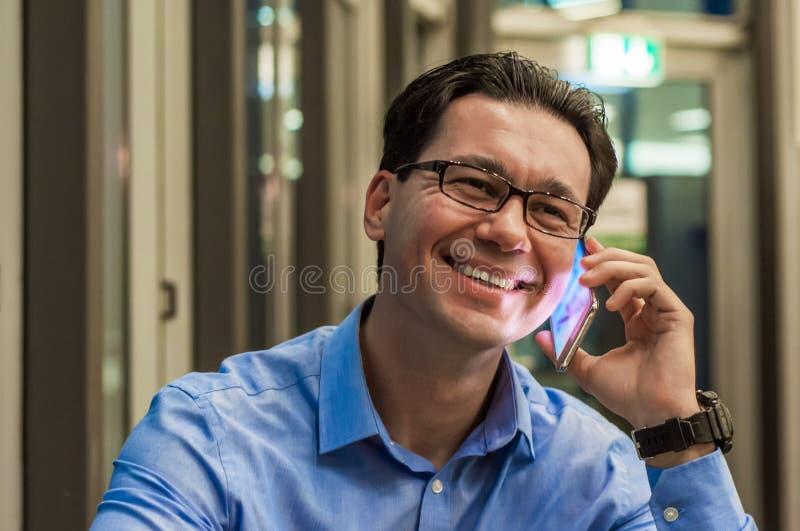 Zamyka up uśmiechnięty biznesmen używać nowożytnego mądrze telefon, Młody szczęśliwy mężczyzna pracuje przy jego biurem i trzyma  obrazy stock
