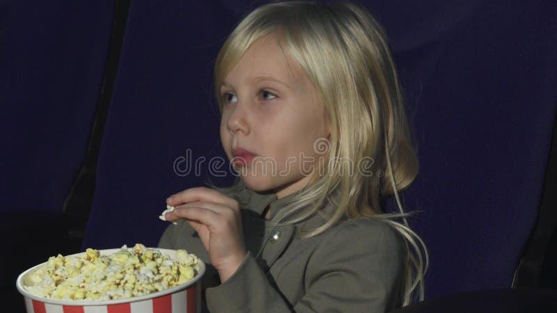 Zamyka up uroczy małej dziewczynki łasowania popkorn podczas gdy przy kinem zdjęcie royalty free